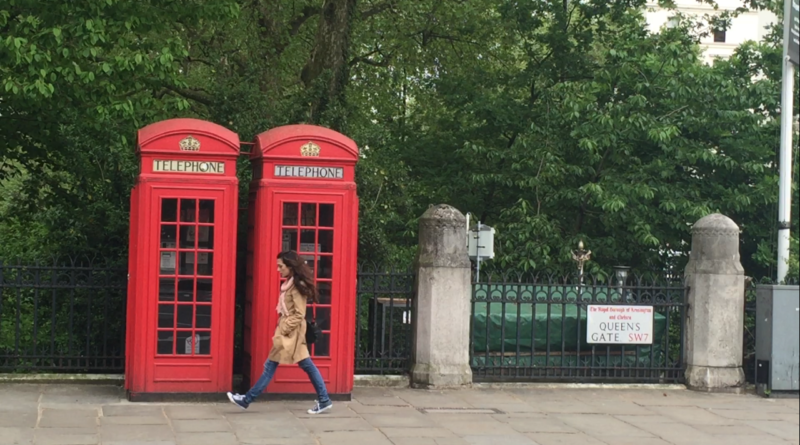 io cammino davanti ad una cabina telefonica in