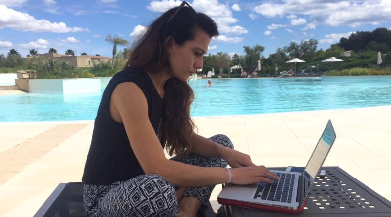 sabrina al computer mentre lavora a bordi piscina